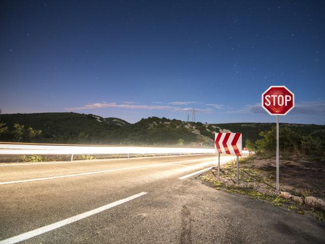 A stop sign on the side of a road at night