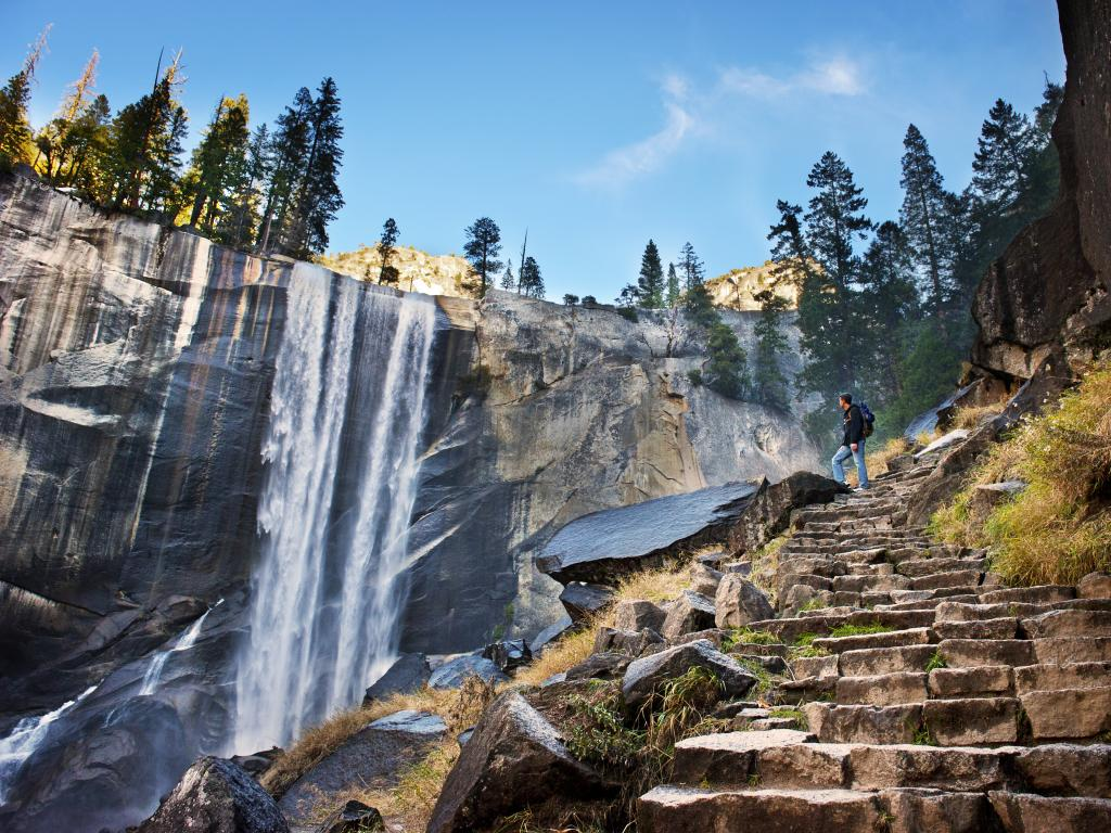 A man at the top of the rock stairs indulges the scenic beauty of the waterfalls in Yosemite National Park.