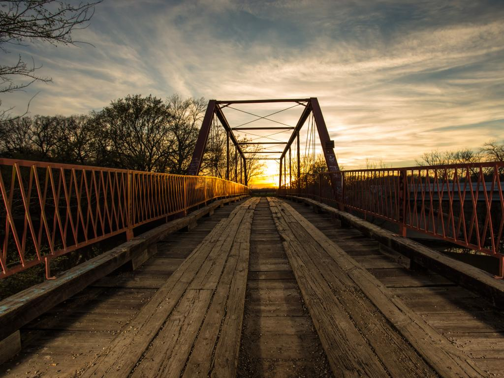 The Old Alton Bridge, also known as the Goatman Bridge, in Denton, Texas at sunset.