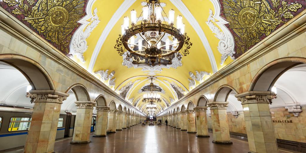 The ornate interior of Komsomolskaya metro station with a yellow Baroque style ceiling and stone arches