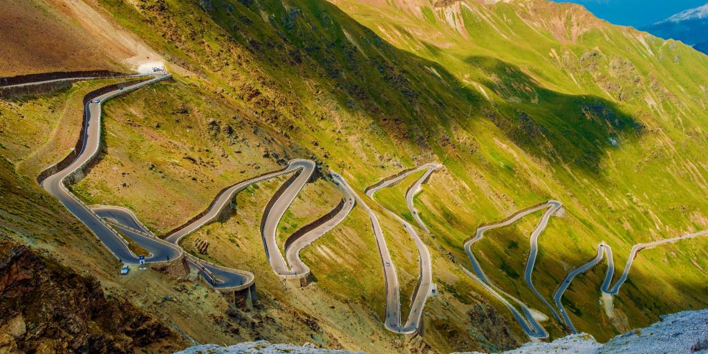 Aerial view of the Stelvio Pass road in the Italian Alps. It is a twisting road on a green mountain.
