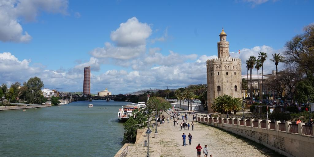 People walk along the banks of the Guadalquivir river in Seville, next to the Torre del Oro
