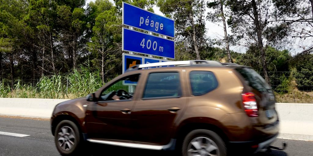 A bronze car on a French road with a blue 'Péage 400m' sign in the background