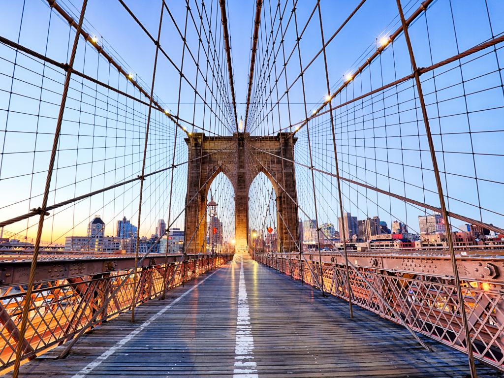 Empty Brooklyn Bridge in New York with buildings on the background and with lights on
