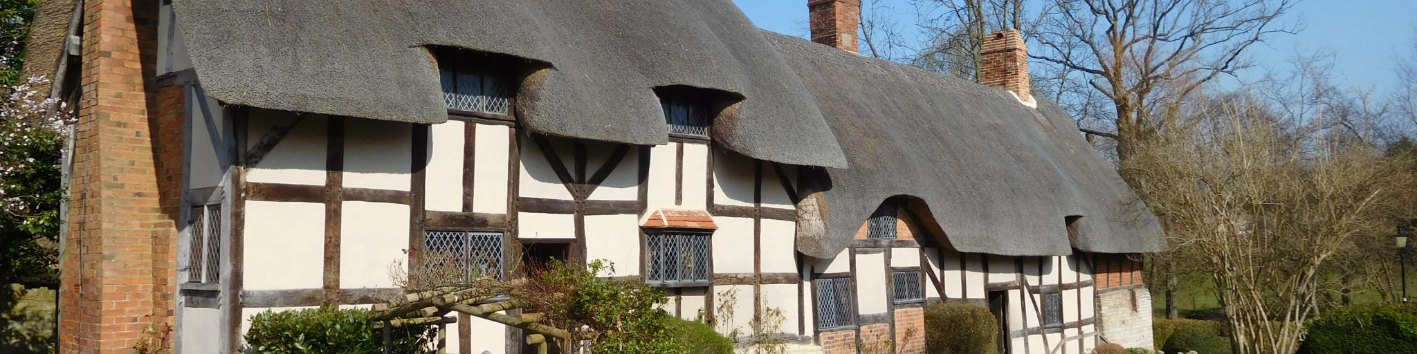 The white thatched cottage of Shakespeare's mother on a sunny day, surrounded by green hedges and trees