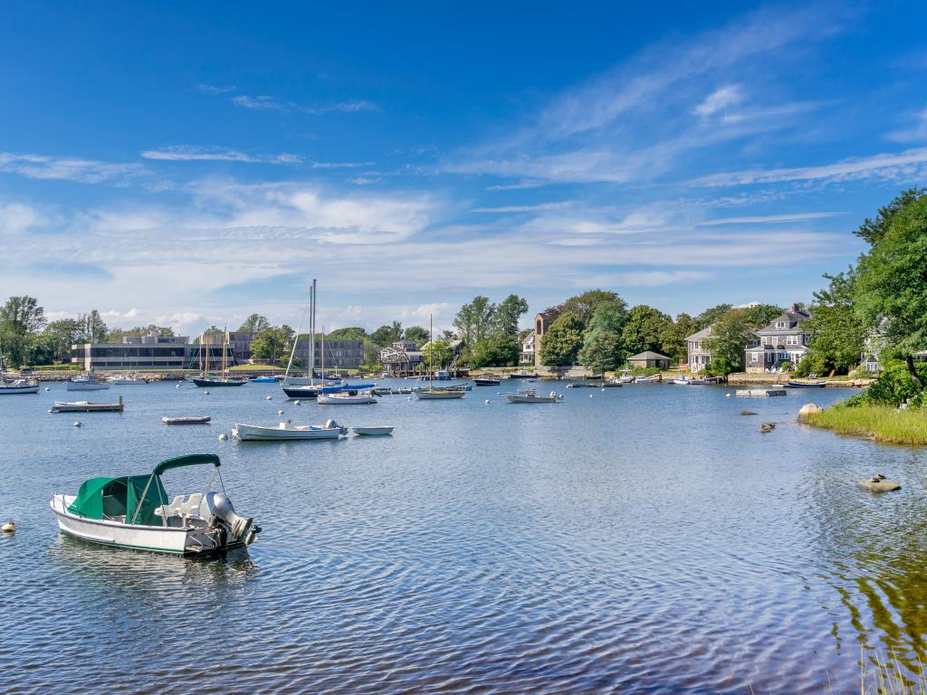 A pleasant day with sheetlike clouds in the sky in Woods Hole, Falmouth and several boats and yachts floating at calm water.