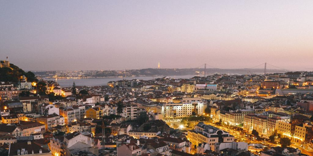 A cityscape view of Lisbon during a purple sunset
