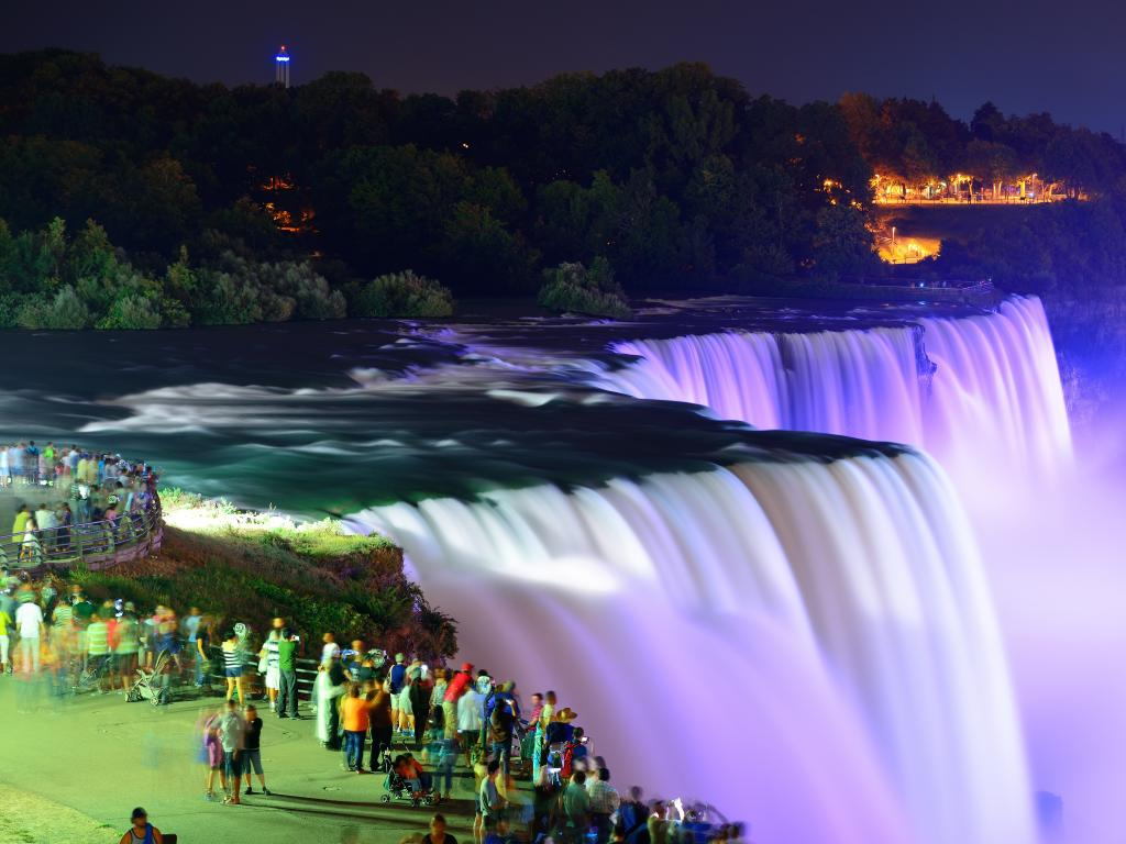 An image where people are looking at the scenic view of Niagara Falls that is enhanced by colorful lights.