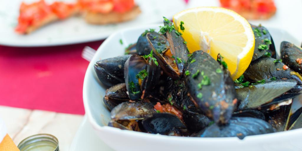 A plate of garnished mussels topped with a slice of lemon