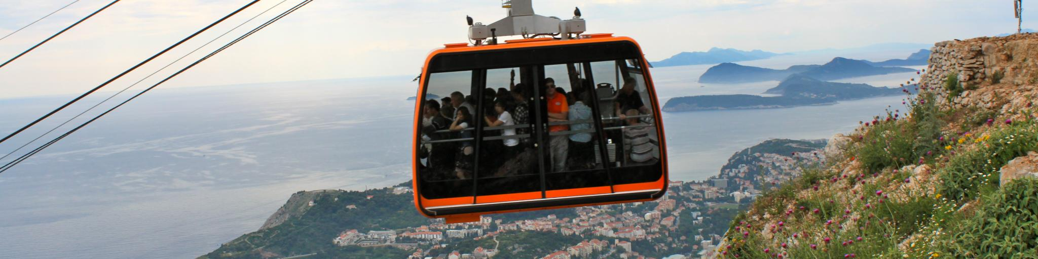 An orange cable car carries passengers up a hill in Dubrovnik, Croatia