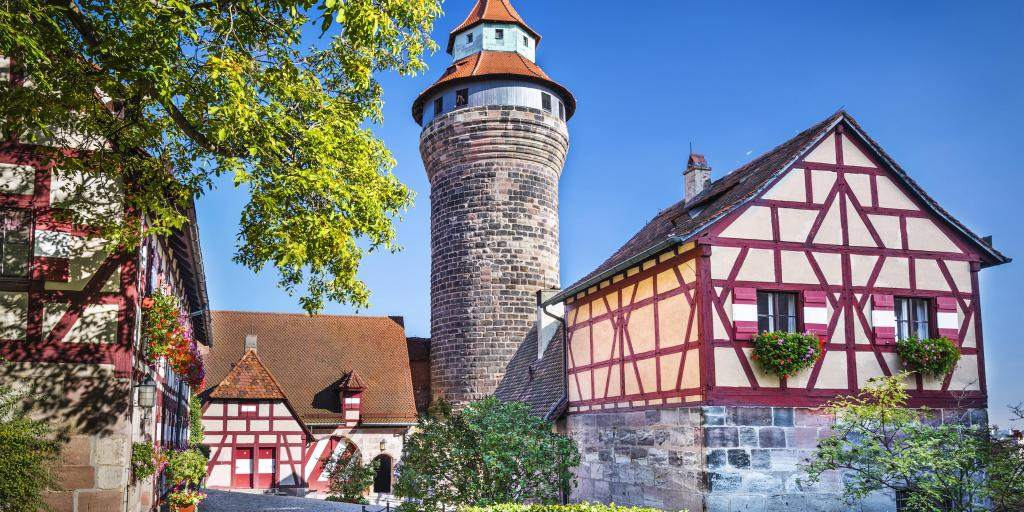 A round tower at Nuremberg Castle, Germany, flanked by two white and red half-timbered buildings, on a sunny day