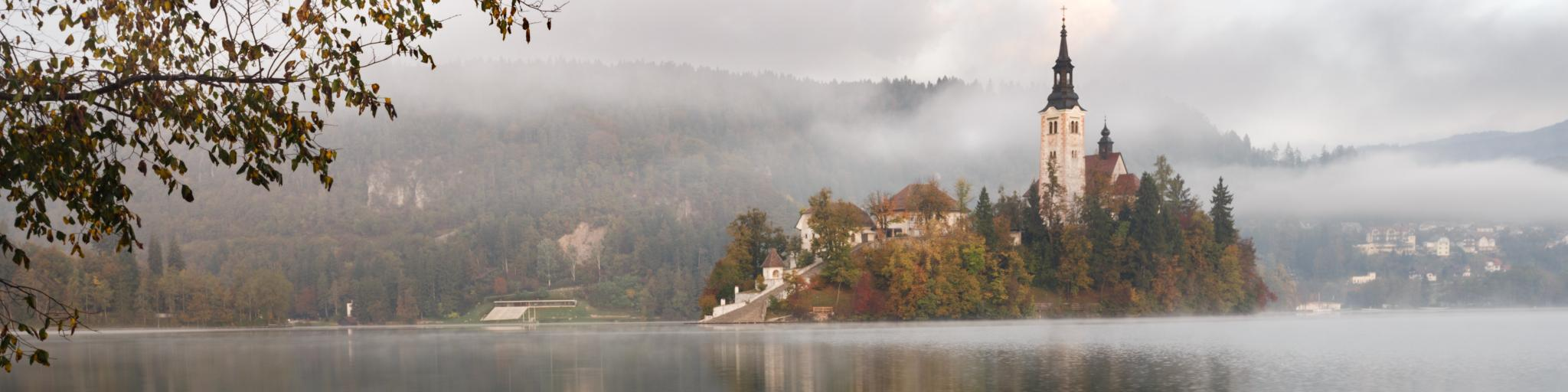 A wooden boat is docked under a tree in front of the famous Bled Castle in Lake Bled