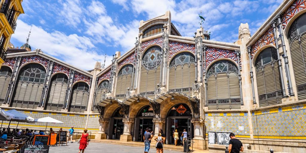 The outside of the Mercado Central in Valencia, Spain, with a pink tiled exterior and arched windows