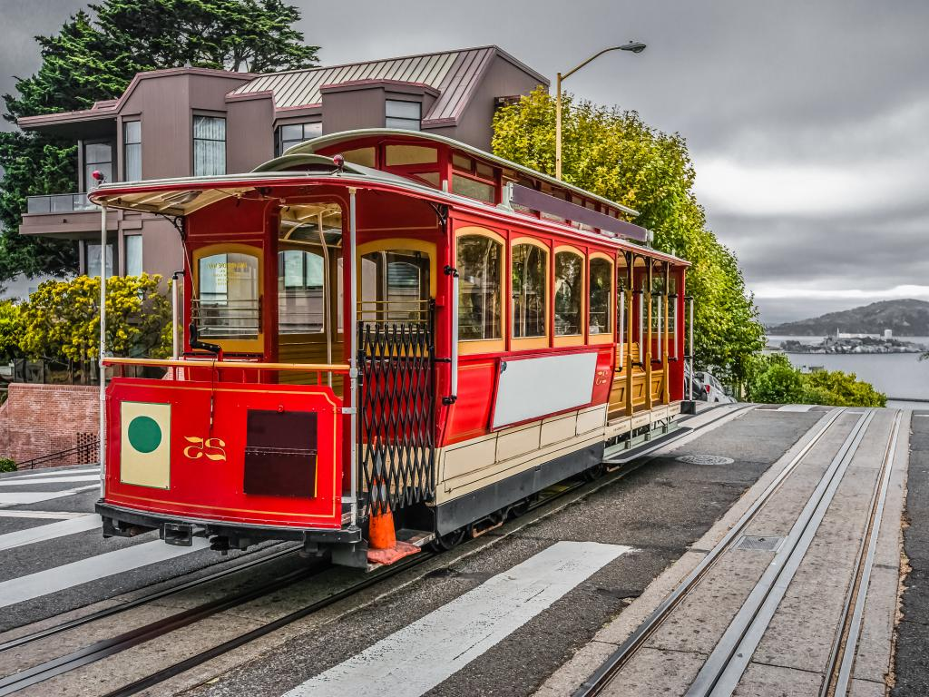 A bright San Francisco cable car on top of a hill with Alcatraz Island in the distance.