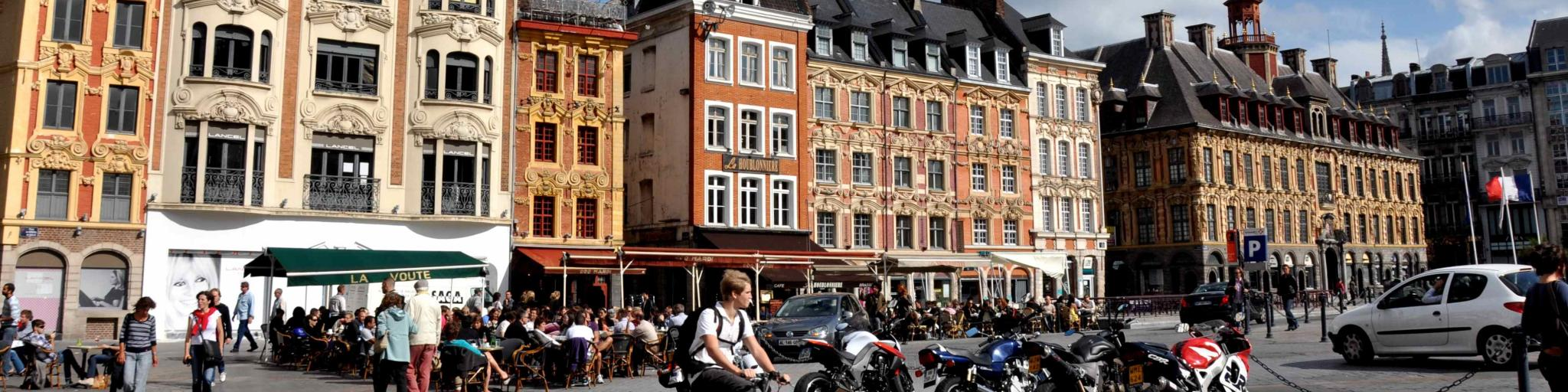 A cyclist bikes across a city square on a sunny day in Lille, France