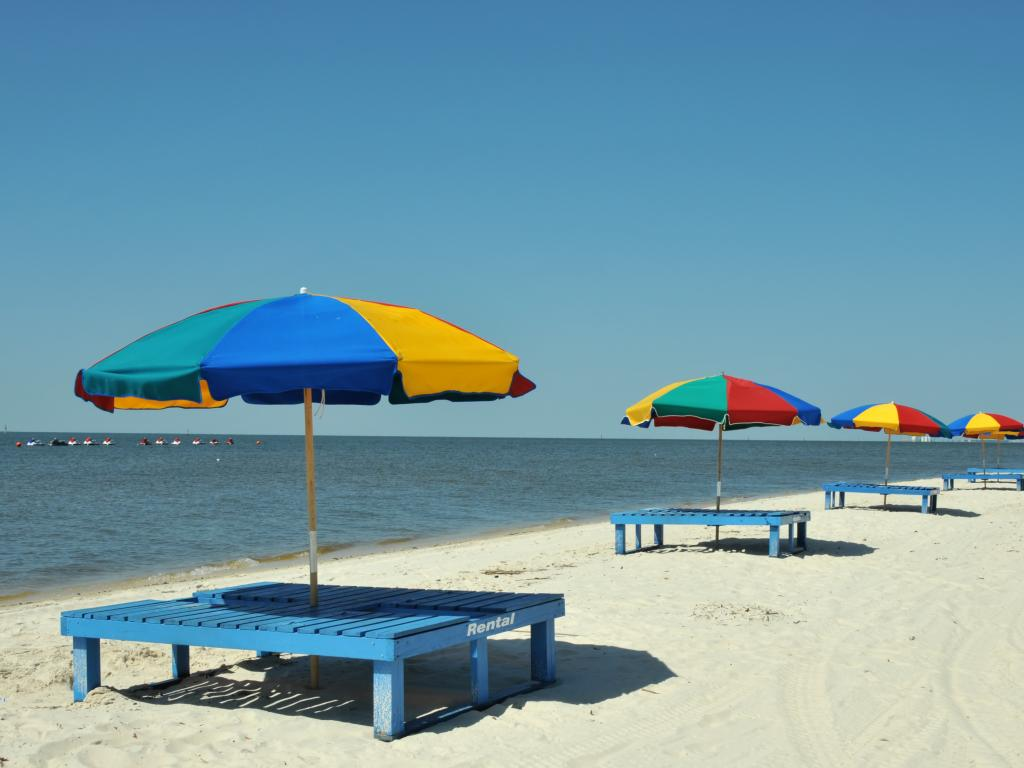 Colorful umbrellas and lounge chairs by the sea in Biloxi Beach near Ocean Springs, Mississippi.