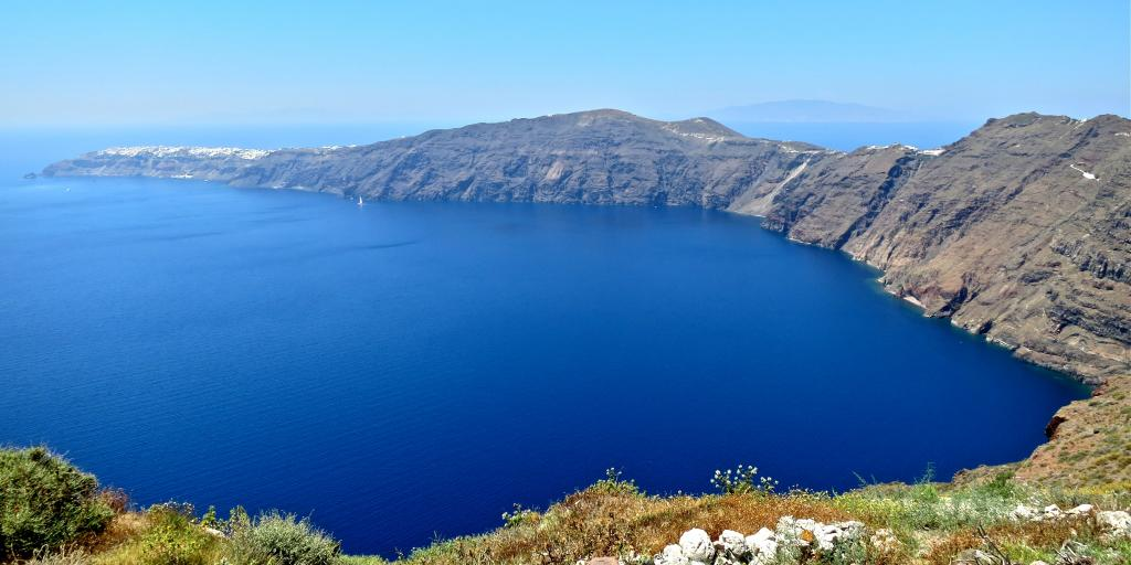 A view of the bright blue caldera in Santorini, Greece, from a high-up vantage point on a hike