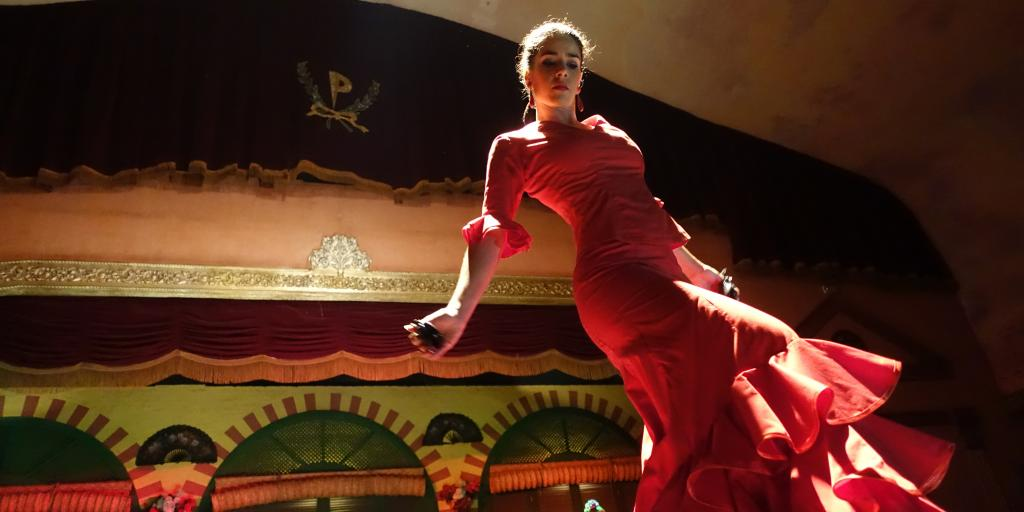 A flamenco dancer in a red dress dances on a stage in Sevilla