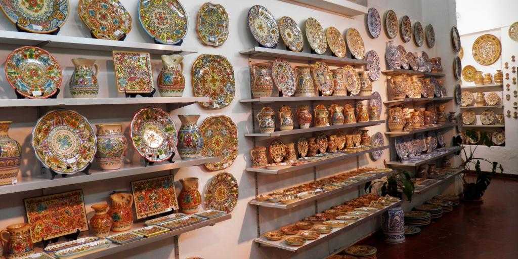 Plates and vases line the shelves inside a ceramics shop in Seville, Spain