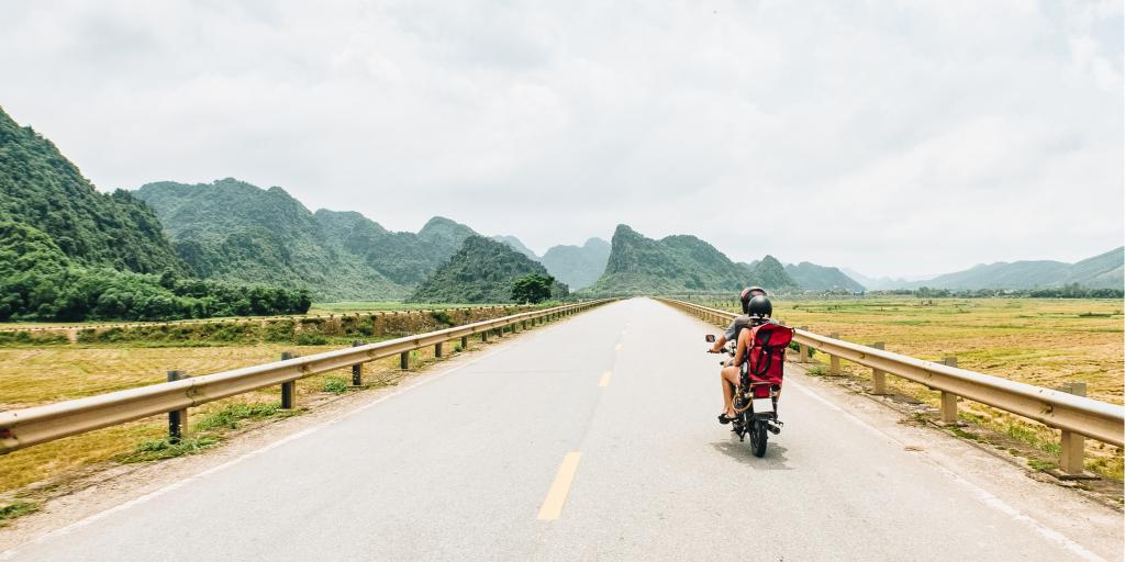 Female motorcyclist drives down a road in Vietnam