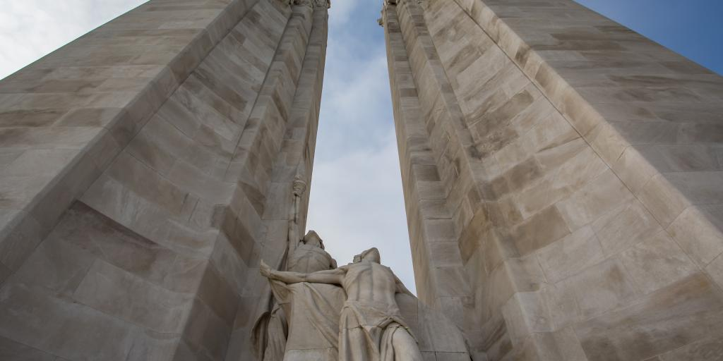 The two towers of the Canadian National Vimy Memorial, France, seen from the bottom, with a sculpture of two people looking up between them