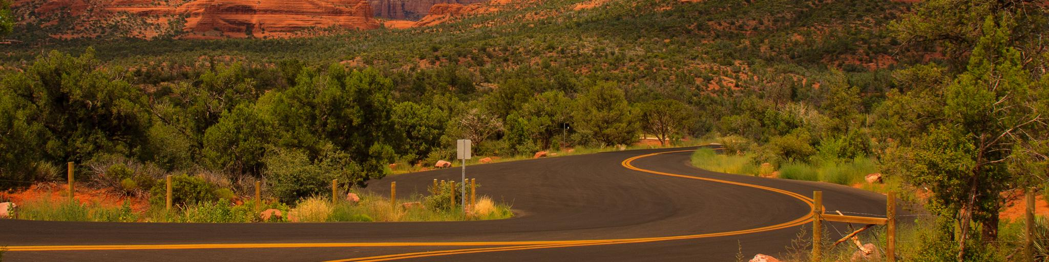 An image of an empty road in Sedona, Arizona during sunset with trees and a view of mountains.
