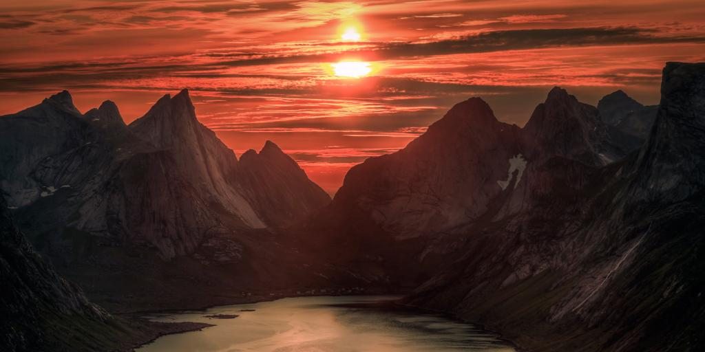 Orange skies caused by midnight sun over Reinebringen mountain, Norway, in summer