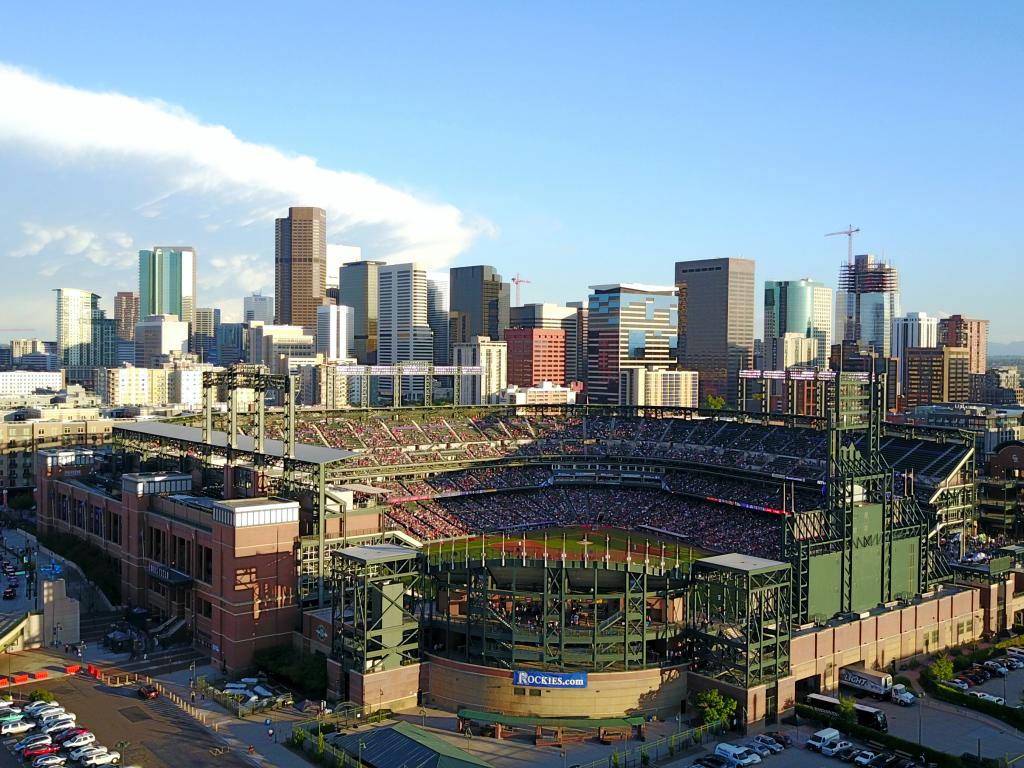 Aerial view of the Coors Field stadium and the Denver city skyline behind it