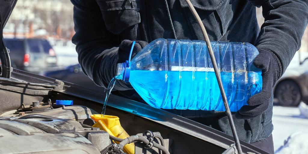 A person in gloves and a coat pouring antifreeze into a coolant system