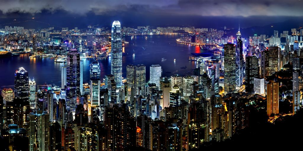 The Hong Kong skyline lit up at night with the harbour in the middle