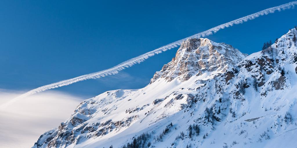 The Rocher de Charvet peak in the resort of Val d'Isere with an aeroplane trail behind it
