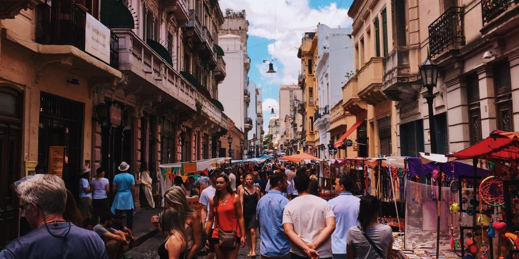People walking through a street market in San Telmo, Buenos Aires, Argentina, with tall colonial buildings each side