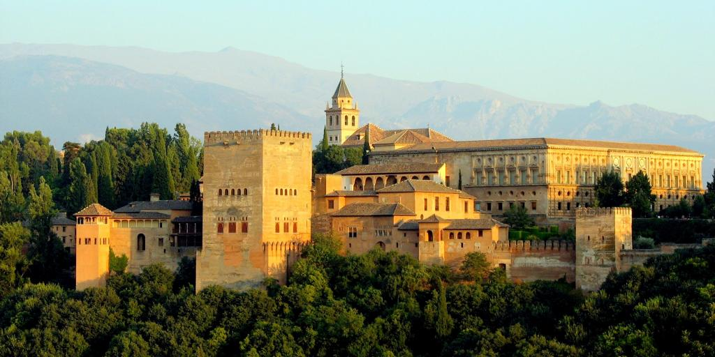 The palatial Alhambra perches on a wooded hill in Granada, Spain, with mountains in the background