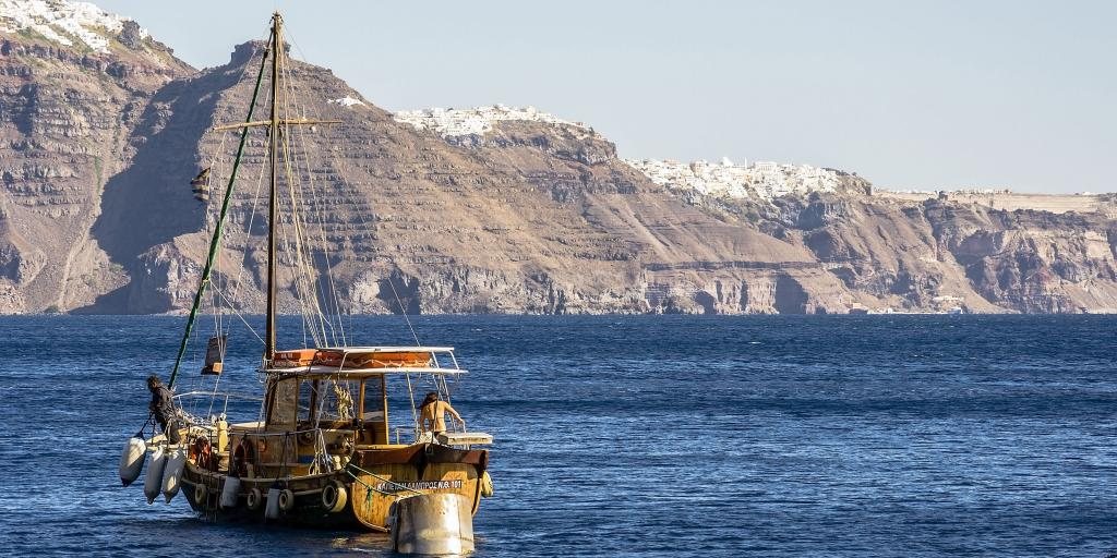 A wooden ship sails in the deep blue water in front of the red cliffs and white villages of Santorini