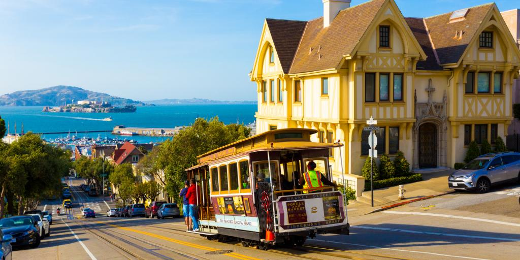 San Francisco cable car tram going downhill with Alcatraz in the background