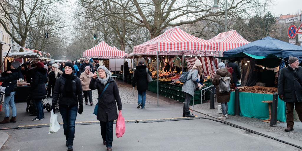 Shoppers carry bags full of produce after visiting the tented stalls at Kollwitzplatz market in Berlin
