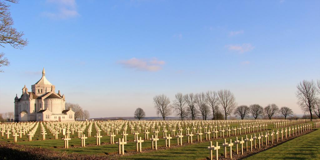 The white chapel at Notre Dame de Lorette Cemetery, France, with rows and rows of graves with white crosses in front and bare winter trees behind