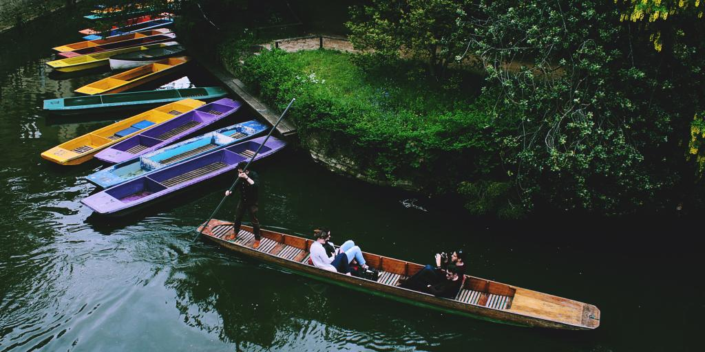 People punting in Oxford next to colourful boats