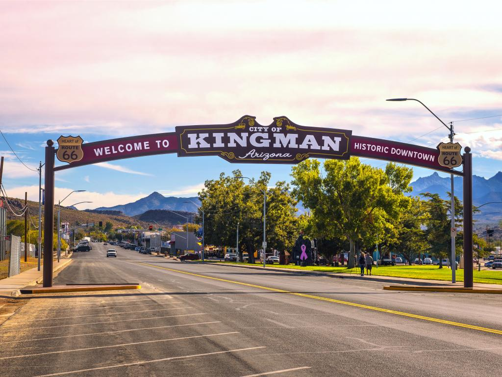 An arches street sign located on historic route 66 Kingman, Arizona with cars driving along the road, people walking in the sidewalk under the shade of trees, and the view of the mountain from the distance