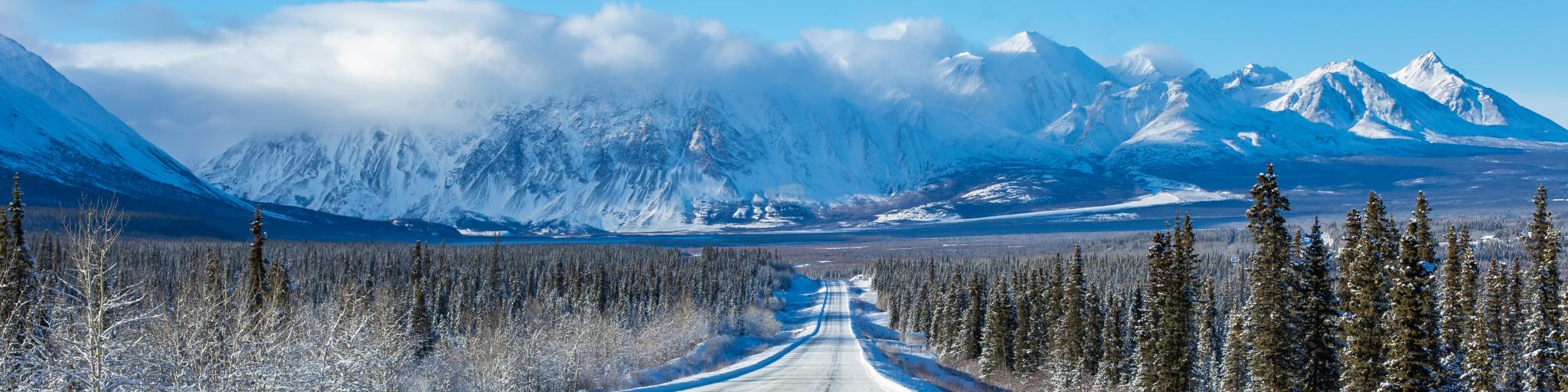 Alaska Highway through the forests of Yukon heading towards mountains in the winter