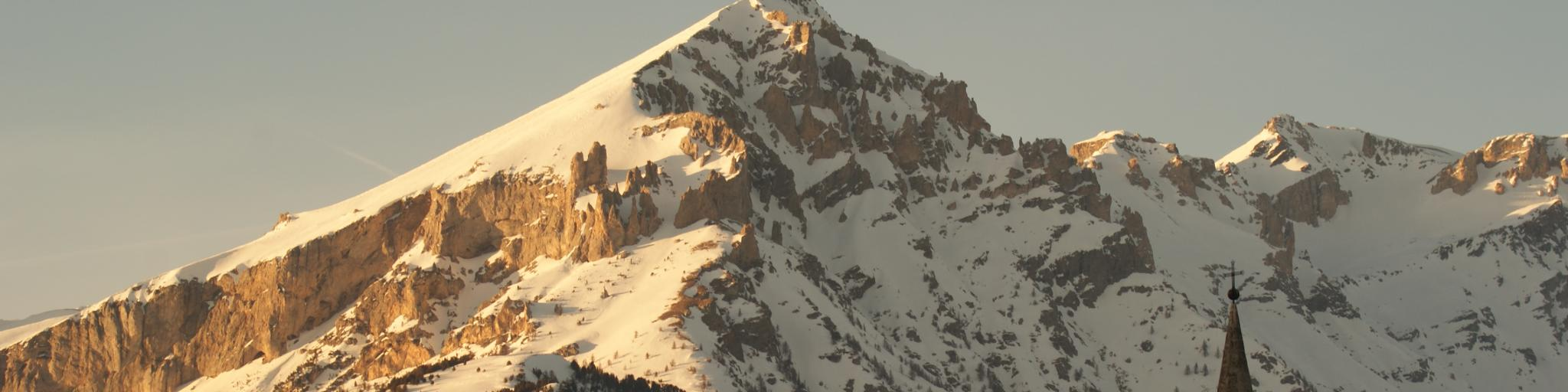 A church steeple in front of snowy mountains in Sauze d'Oulx, Italy