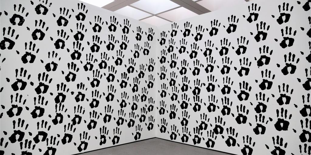 A wall of black hand prints on a white wall that turns at a right angle