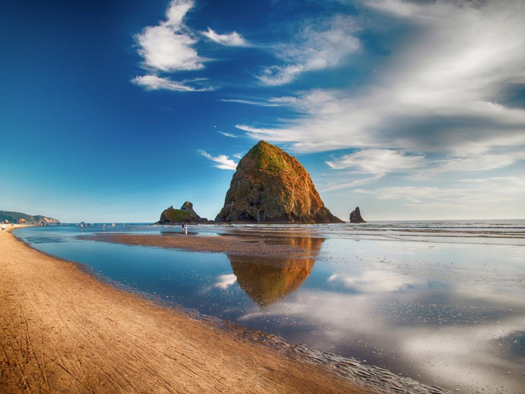 Haystack Rock and its reflection on the water in Cannon Beach, Oregon