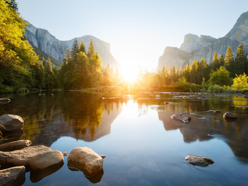 Sunrise through Yosemite Valley with the Merced River in the foreground.