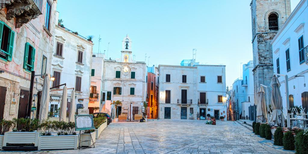 A square lined with white-washed buildings in Polignano a Mare, Puglia