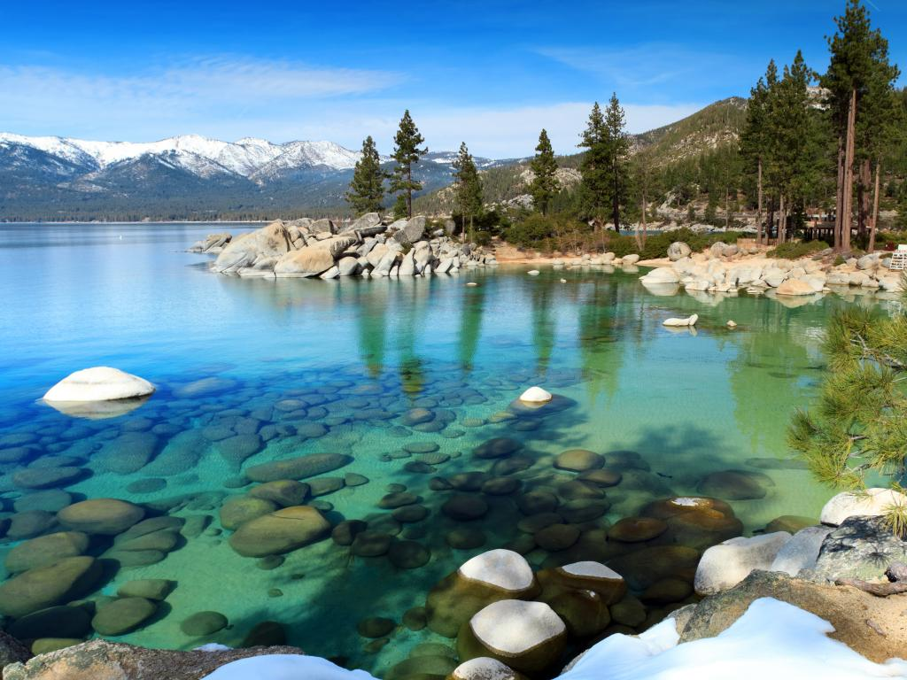 Clear waters of Lake Tahoe with snow covered mountain peaks in the background, California - Nevada border