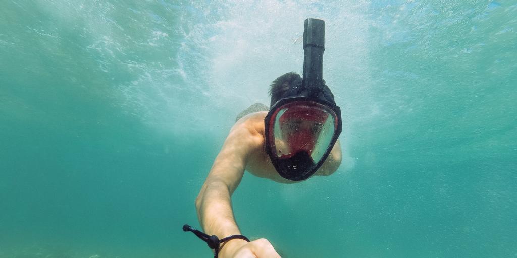 An underwater selfie by a man wearing a full face snorkelling mask, taken using a selfie stick