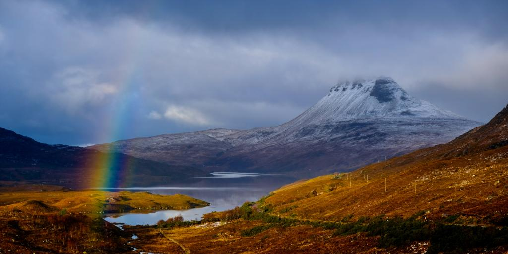 Stac Pollaidh Mountain, Scotland, coated in snow on a cloudy day, with a rainbow and a loch in front