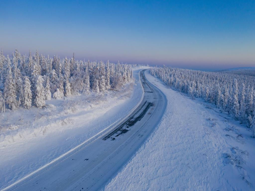 The Dalton Highway ice road in the middle of the winter passing through a conifer forest in northern Alaska.