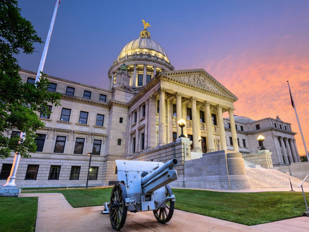 The State Capitol building in Jackson Mississippi with a classic cannon in front at sunset.